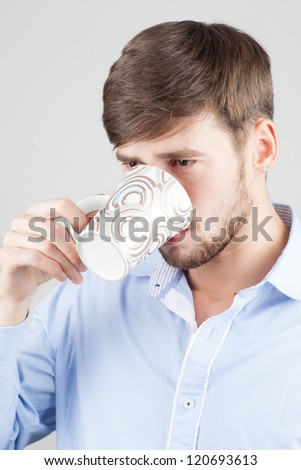 Young, handsome man drinking from a mug - stock photo