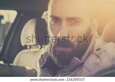 Young handsome man driving his car on a beautiful sunny day. Retro tones. - stock photo