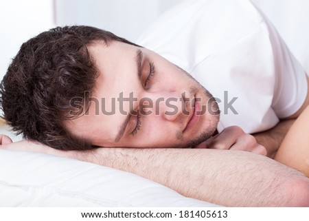 Young handsome man during sleeping in bed - stock photo