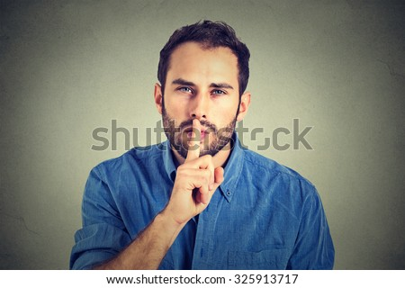 young handsome man giving Shhhh quiet, silence, secret gesture isolated on gray wall background   - stock photo