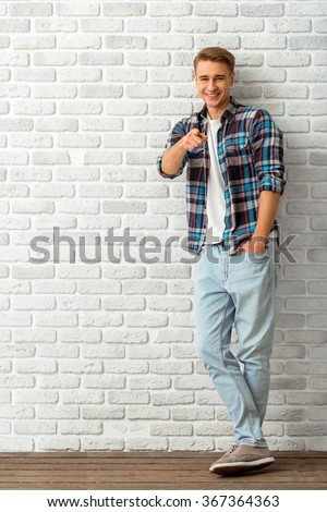 Young handsome man in a checkered shirt and denim pants, keep a hand in his pocket, smiling and looking at the camera, standing on the brick wall background - stock photo