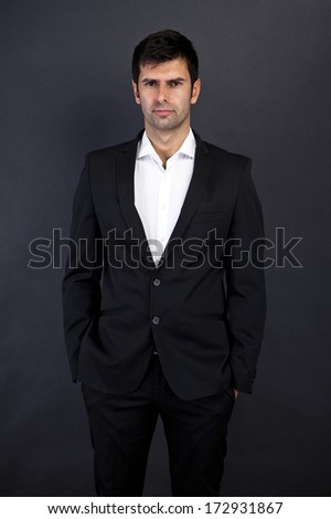 Young handsome man in black suit smiling on dark background - stock photo