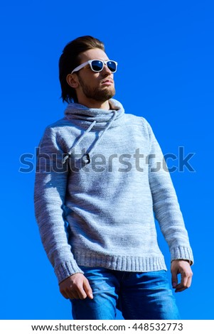 Young handsome man in casual clothes and sunglasses over blue sky. Men's beauty, fashion. Outdoor portrait. - stock photo