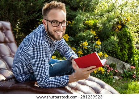 Young handsome man in casual clothes & glasses sit in luxury sofa in summer garden. - stock photo