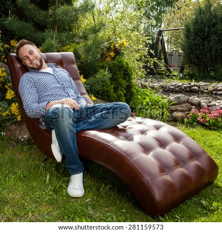 Young handsome man in casual clothes sit in luxury sofa in summer garden. - stock photo