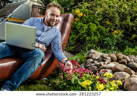 Young handsome man in casual clothes sit in luxury sofa with notebook in summer garden. - stock photo