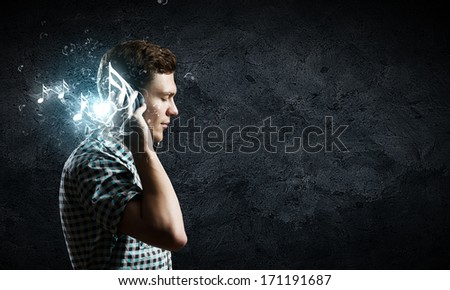 Young handsome man in earphones enjoying the music - stock photo