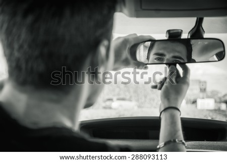 Young handsome man in his car adjusting rear view mirror during day - stock photo