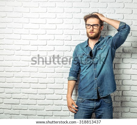 Young handsome man in jeans shirt standing on white brick background - stock photo