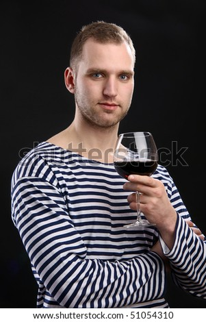 Young handsome man in sailor's jacket holding a glass of wine - stock photo