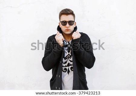Young handsome man in sunglasses and a sweater on a white background. - stock photo