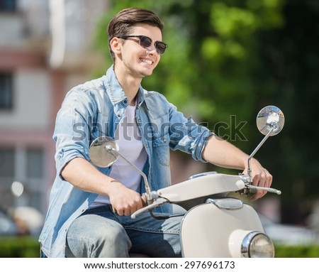 Young handsome man in sunglasses riding scooter on sunny day. Side view. - stock photo
