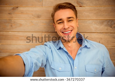 Young handsome man in the blue shirt, lying on the wooden floor, smiling, taking pictures of themselves. Close-up - stock photo