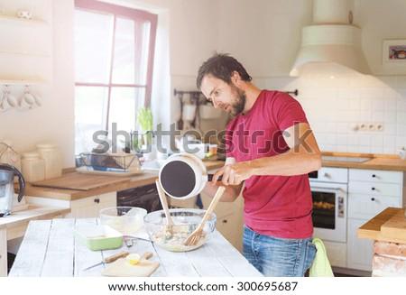 Young handsome man in the kitchen preparing salmon tagliatelle - stock photo