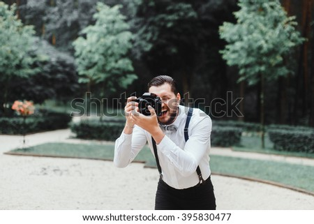 young handsome man in white shirt and trousers makes beautiful pictures on film retro camera, stylishly dressed, photographer,outdoor portrait, close up - stock photo