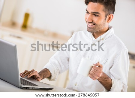 Young handsome man in white shirt drinking tea and using laptop in the morning. - stock photo
