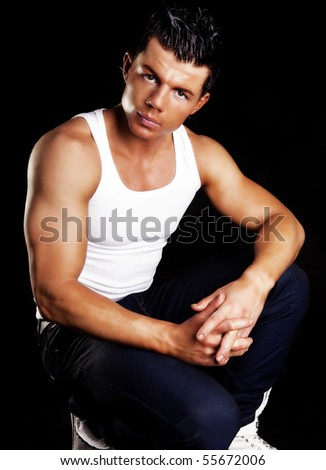 young handsome man in white shirt posing over dark background - stock photo