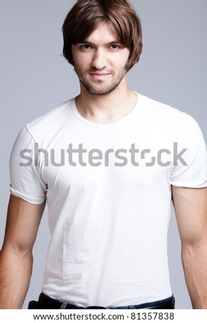 young handsome man in white t-shirt, studio shot - stock photo