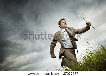 Young handsome man is running on the lace. He keeps in the hands of wild flowers. Swain. - stock photo