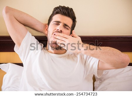Young handsome man is waking in morning. Attractive guy is stretching and yawning in bed. - stock photo