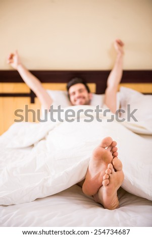 Young, handsome man is waking up fully rested. - stock photo