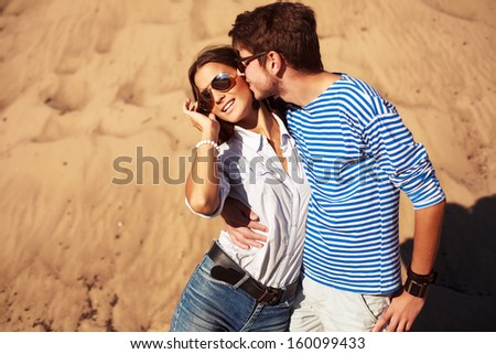 Young handsome man kissing his girlfriend in summer  - stock photo
