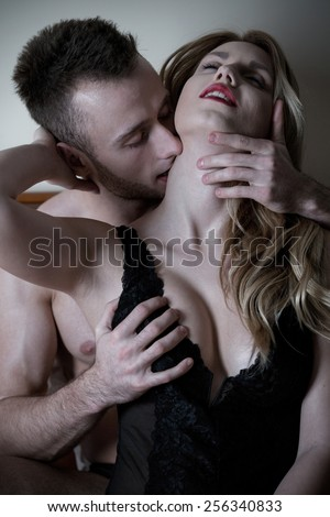 Young handsome man kissing his sexy woman's neck - stock photo