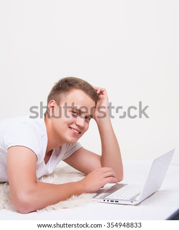 Young handsome man lies on a white background with a white laptop. Learning language, learning, leisure, watching movies - stock photo