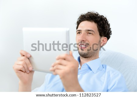Young handsome man looking on a modern digital tablet. Studio shot. - stock photo