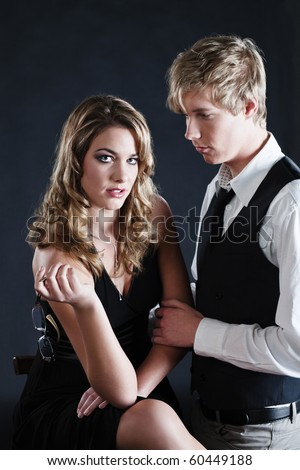 Young handsome man looks at pretty woman and touches her hand - stock photo