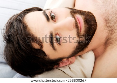 Young handsome man lying in bed. - stock photo