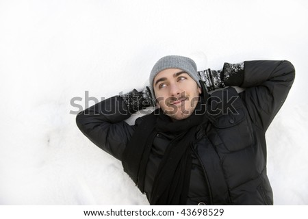 Young handsome man lying on snow. - stock photo