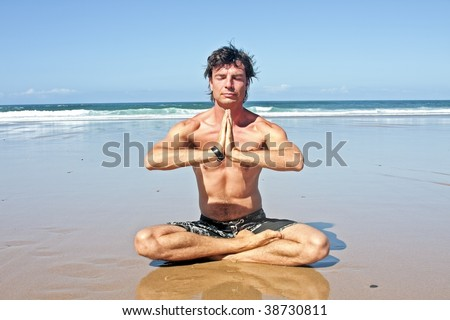 Young handsome man meditating on the beach sitting in lotus position: Namaste! - stock photo