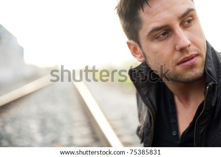 Young handsome man on railway - stock photo