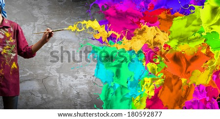 Young handsome man painter with brush in hand - stock photo