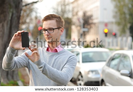 Young handsome man photographing with mobile smart phone walking, background is blurred city - stock photo