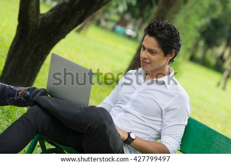 Young handsome man portrait while working with laptop in Lumpini Park. Bangkok, Thailand. - stock photo