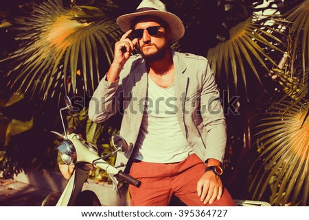 young handsome man posing in the street with  retro scooter - stock photo