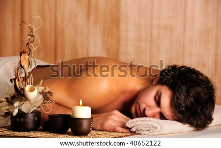 Young handsome man relaxing in spa salon - high angle view - stock photo