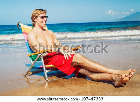 Young Handsome Man Relaxing on Tropical Beach - stock photo