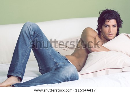 Young handsome man shirtless , embraced to pillow ,  in a sensual pose on bed. - stock photo