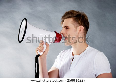 Young handsome man shouting in megaphone. - stock photo