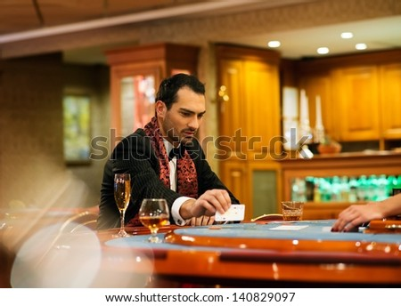 Young handsome man sitting behind poker table with card - stock photo