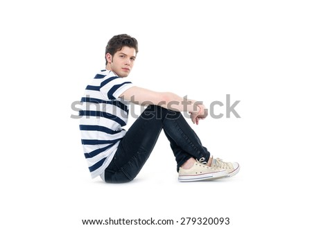 young handsome man sitting floor . Studio fashion portrait - stock photo