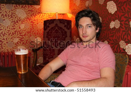 Young handsome man sitting in a bar drinking beer - stock photo