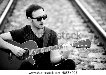 Young handsome man sitting in railway and playing guitar. - stock photo