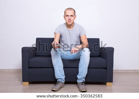 young handsome man sitting on sofa and watching tv at home - stock photo