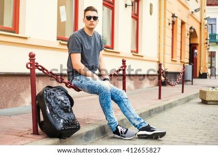 Young handsome man sitting on the street. Dressed in a T-shirt, jeans, fashion sneakers, with a backpack in the form of a lion, sunglasses, Hipster style guy - stock photo
