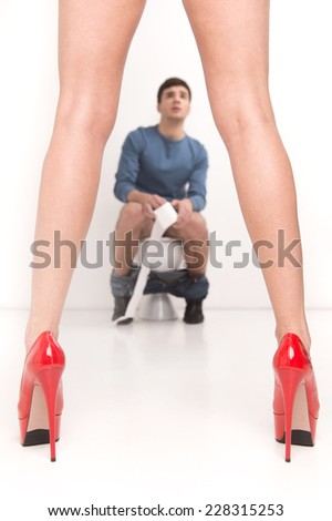Young handsome man sitting on toilet. woman standing in front of man sitting in bathroom - stock photo