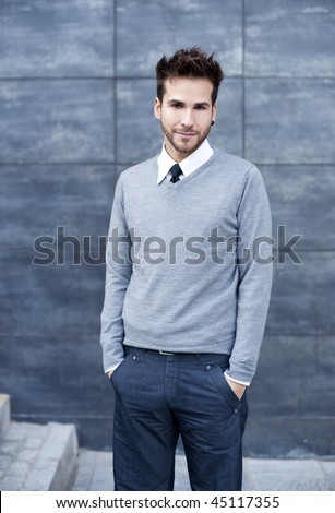 Young handsome man standing against wall - stock photo